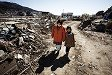 Kaue Atsumi, 58, a !sh processing factory worker, and her grand daughter Moeka Abe, 7, walk through the devastated whaling town of Ayukawa, near the city of Ishinomaki, Japan after visiting Atsumi's father at nursing home on March 24, 2011. by Ko Sasaki