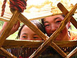 Two girls looking in through the lattice wall of a yurt being set up